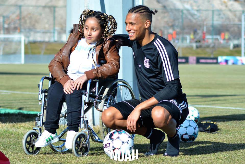 A fan using a wheelchair meets an FC Noah player at the training ground. The male player crouches down to be at eye level with the disabled fan.