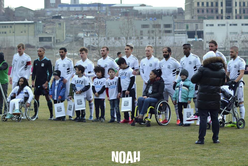 Disabled fans on the pitch alongside FC Noah players before kick off. Everyone is wearing CAFE t-shirts for the occasion.