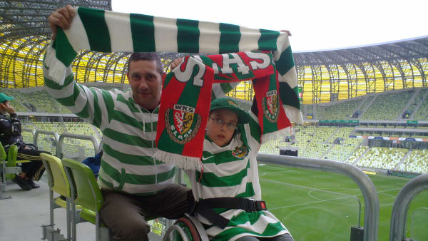 Marek, a disabled fan, with his dad holding Lechia Gdansk scarves