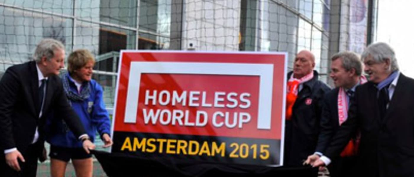 Stakeholders gathered around a Homeless World Cup banner